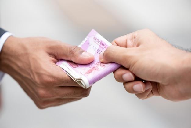 Mano dell'uomo d'affari che dà soldi valuta della rupia indiana al suo partner Foto Premium