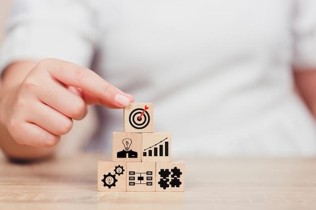 Mano dell'uomo d'affari che mette blocco di cubo di legno sulla cima con il concetto di successo dell'obiettivo. Foto Premium