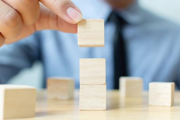 Mano dell'uomo d'affari che organizza il blocco di legno che impila sulla cima con la tavola di legno. Foto Premium