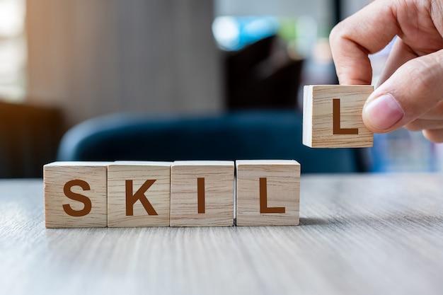 Mano dell'uomo d'affari che tiene il blocchetto di cubo di legno con la parola di affari di parola. abilità, impara, conoscenza, tecnica, professionale ed esperienza Foto Premium