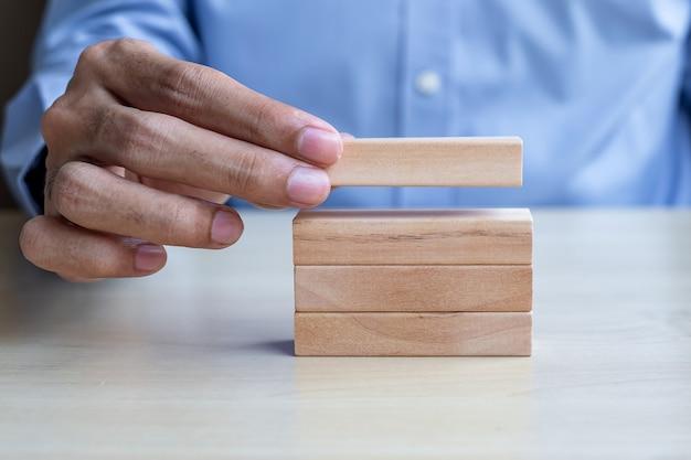 Mano dell'uomo d'affari che tiene le particelle elementari di legno sulla tavola Foto Premium