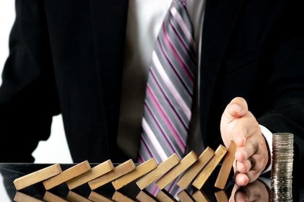 Mano dell'uomo d'affari del primo piano che ferma i blocchi di legno dalla caduta sulle monete impilate sopra lo scrittorio Foto Premium