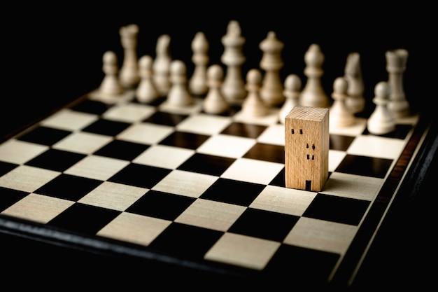 Mano dell'uomo di affari che sposta gli scacchi a costruire e ad alloggiare i modelli nel gioco di scacchi Foto Premium