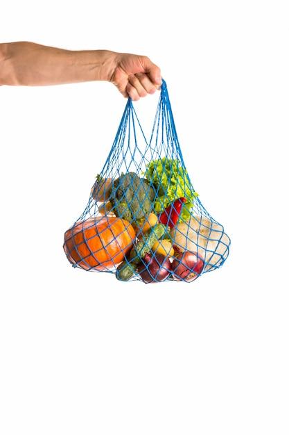 Mano dell'uomo irriconoscibile che tiene un sacco di verdure miste. cibo sano e concetto di rifiuti zero. isolato su bianco Foto Premium