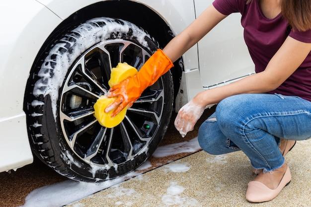 Mano della donna che indossa i guanti arancio con l'automobile moderna della ruota gialla di lavaggio della spugna Foto Premium