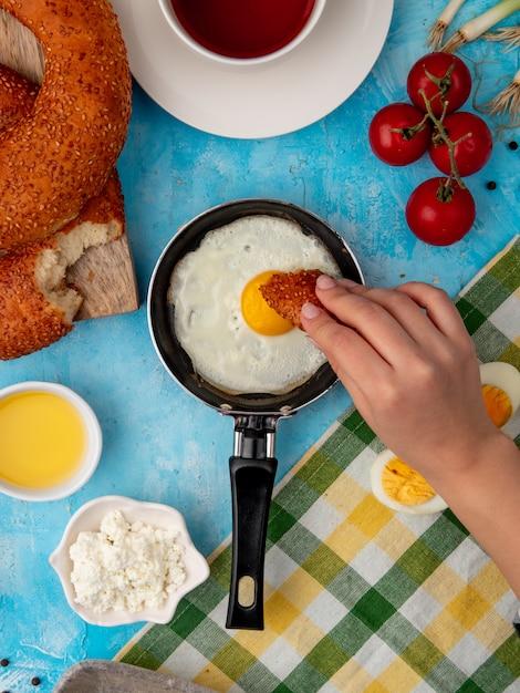 Mano della donna che mangia pane con l'uovo fritto Foto Gratuite