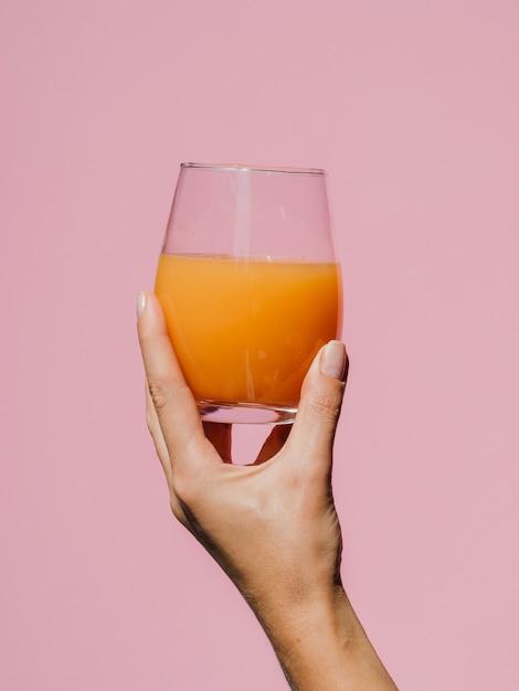Mano della donna che tiene un bicchiere di succo saporito Foto Gratuite