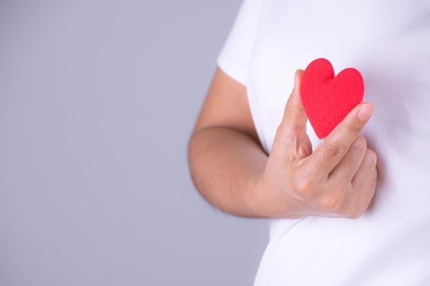 Mano della donna che tiene un cuore rosso. concetto di giornata mondiale del cuore. Foto Premium