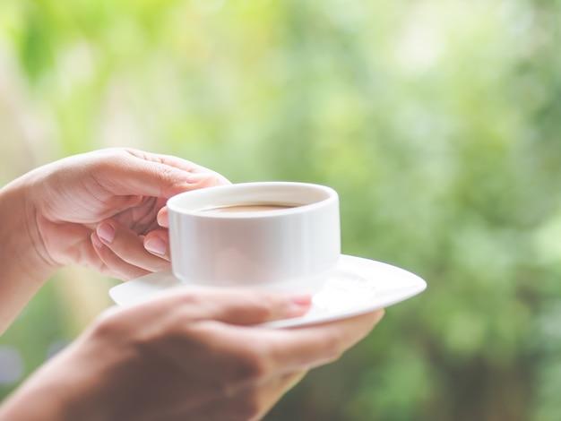 Mano della donna che tiene una tazza di caffè al giardino di mattina Foto Premium