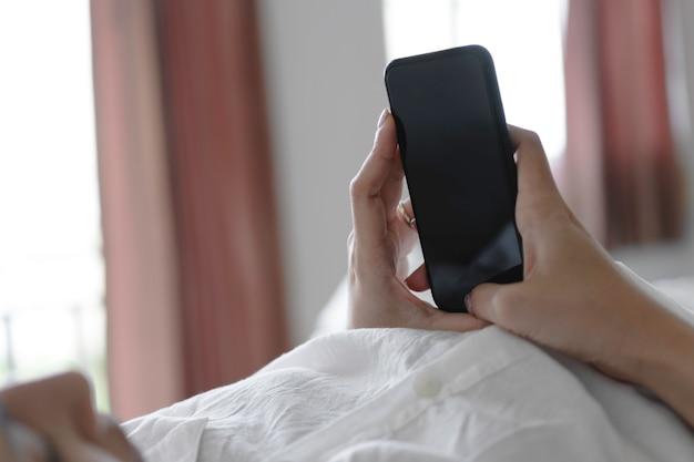 Mano della donna che utilizza smartphone con lo schermo in bianco mentre si trovava a letto al mattino. Foto Premium