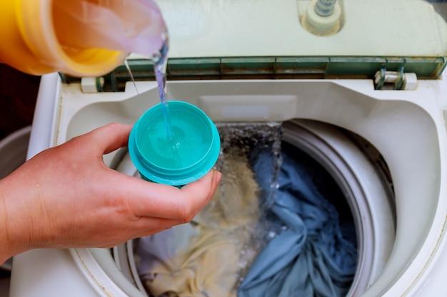 Mano della donna che versa detersivo nella lavatrice Foto Premium