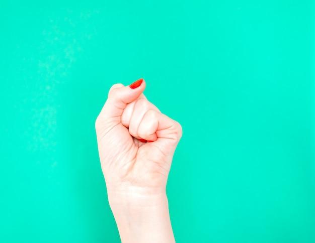 Mano della donna con il pugno chiuso sul fondo isolato di colore verde del turchese. Foto Premium