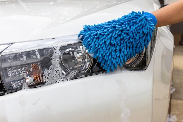 Mano della donna con l'automobile moderna del faro di lavaggio del tessuto blu del microfiber o l'automobile di pulizia. Foto Premium