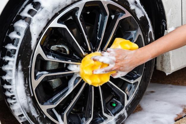 Mano della donna con l'automobile moderna della ruota di lavaggio gialla della spugna o l'automobile di pulizia. Foto Premium