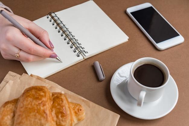 Mano della donna con scrittura a penna sul taccuino alla caffetteria. libero professionista che lavora all'aperto. pausa caffè con cornetto Foto Premium