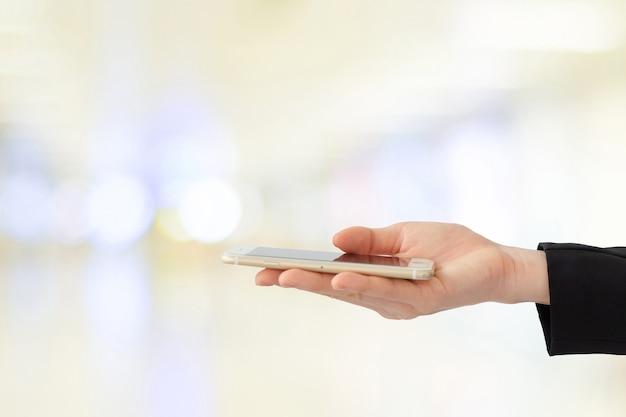 Mano della donna di affari facendo uso dello smart phone sopra l'ufficio della sfuocatura con il fondo della luce del bokeh, insegna, affare sul telefono Foto Premium