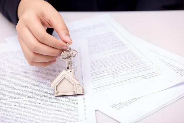 Mano della donna e chiave domestica. contratto firmato e chiavi della proprietà con documenti Foto Premium