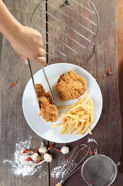 Mano della donna ed ali di pollo fritto con le patate fritte sulla tavola di legno. Foto Premium