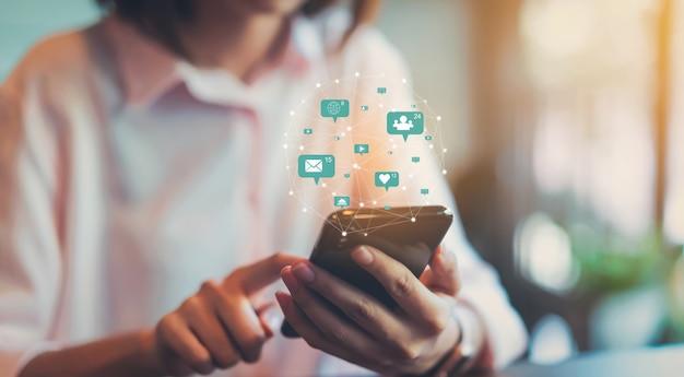 Mano della donna facendo uso dei media sociali dell'icona di tecnologia di manifestazione e dello smartphone. concetto di social network. Foto Premium