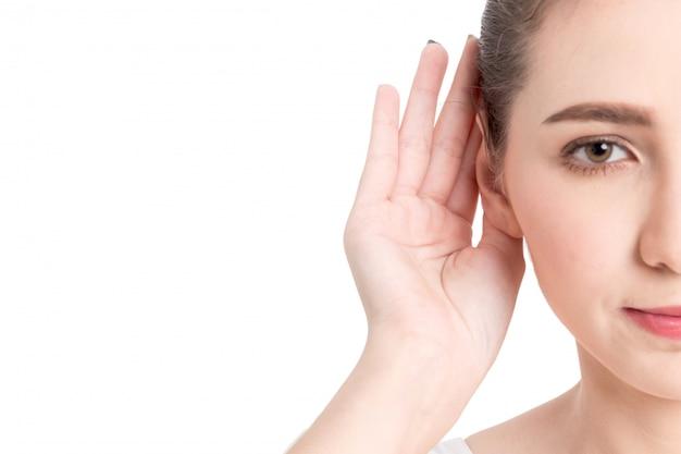Mano della donna sull'orecchio che ascolta per il suono calmo isolato su fondo bianco Foto Premium