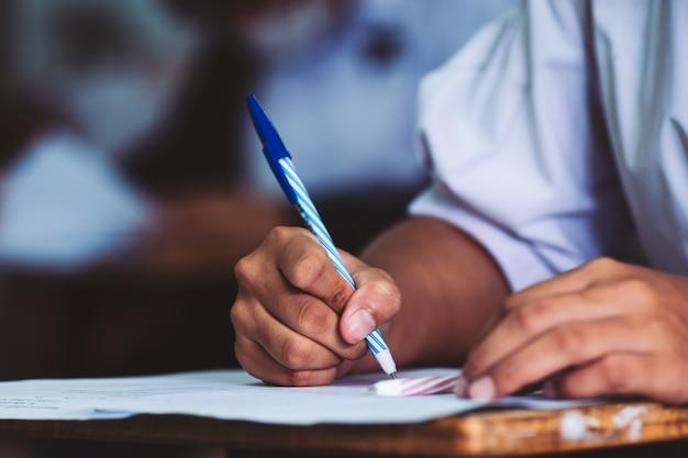 Mano della penna di tenuta dello studente e l'esame in classe con lo stress Foto Premium