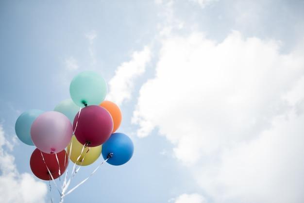 Mano della ragazza che tiene i palloni variopinti Foto Gratuite
