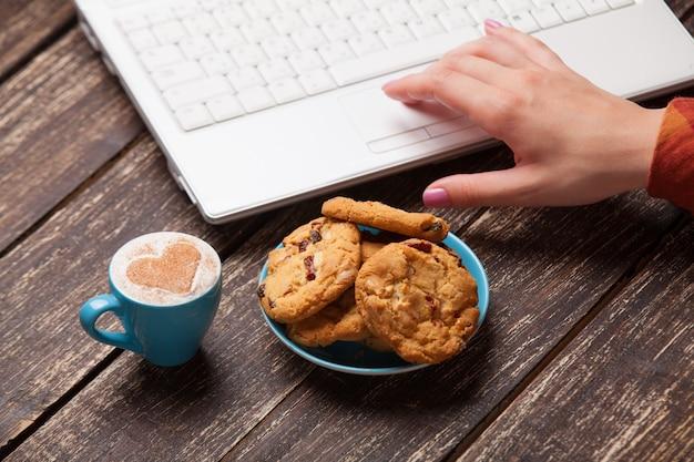 Mano delle donne e del biscotto con il taccuino. Foto Premium