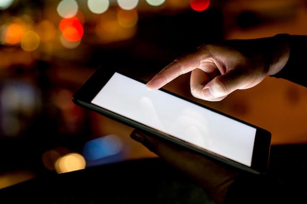 Mano destra dello schermo d'ardore commovente dell'uomo asiatico della compressa del computer durante la notte con le luci della città. focus nella sua mano. profondità di campo Foto Premium