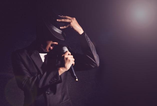 Mano di cantante che tiene il microfono e cantando su sfondo nero Foto Premium