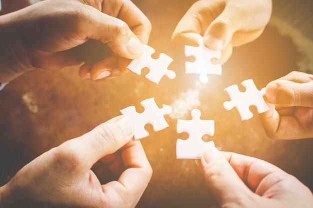 Mano di diverse persone che collegano jigsaw puzzle. concetto di partnership e lavoro di squadra nel mondo degli affari Foto Premium