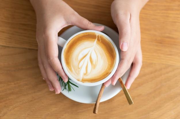 Mano di donna che tiene una tazza di caffè bianco. il caffè è un latte. tavolo sul tavolo di legno Foto Premium