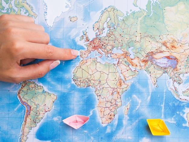Mano di donna vista dall'alto che punta su un luogo sulla mappa Foto Gratuite