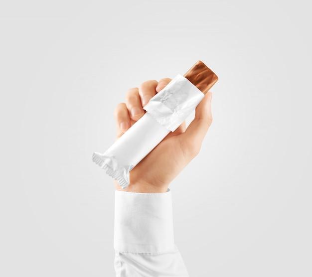Mano di stretta aperta dell'involucro di plastica bianco vuoto della barra di caramella Foto Premium