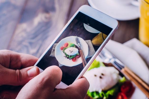 Mano di uomini che prendono cibo per foto con lo smartphone mobile Foto Premium