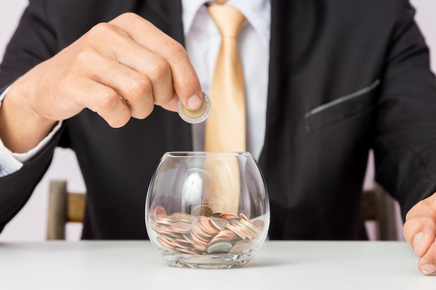 Mano di uomo d'affari che mette le monete sul vetro Foto Premium