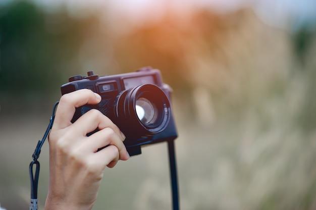 Mano e macchina fotografica del fotografo tenendo e portando la fotocamera per scattare foto Foto Premium