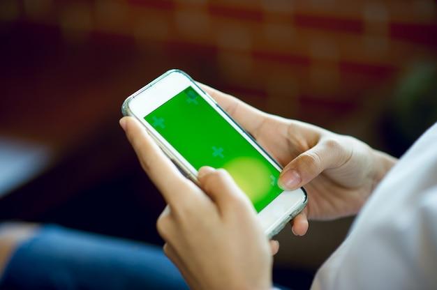 Mano e telefono della ragazza che fa concetto di comunicazione online e commerciale di affari con lo spazio della copia. Foto Premium