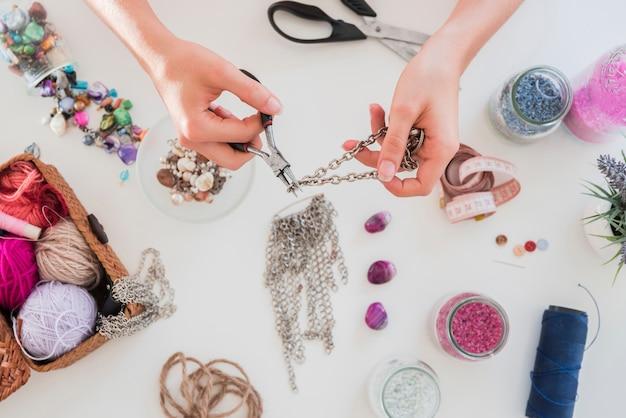 Mano facendo e tagliando la catena metallica sulla scrivania bianca con perline Foto Gratuite
