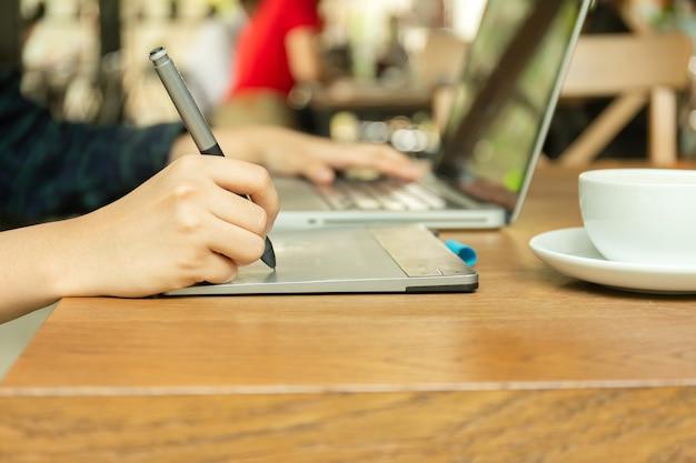 Mano facendo uso della compressa digitale e dello stilo penand che funzionano con il computer portatile. Foto Premium