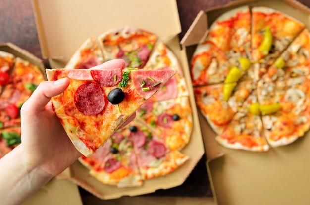 Mano femminile che prende fetta di pizza fresca dalla scatola di consegna. vista dall'alto, sfondo scuro. cibo spazzatura Foto Premium