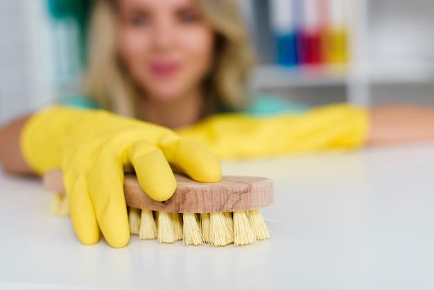 Mano femminile che pulisce scrittorio bianco con la spazzola di legno Foto Gratuite