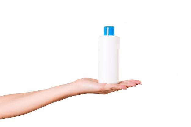 Mano femminile che tiene la bottiglia di crema di lozione Foto Premium