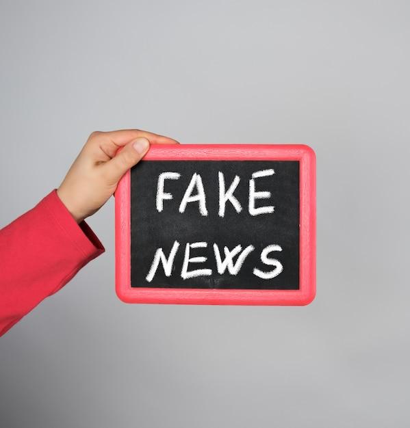 Mano femminile che tiene struttura rossa con notizie false dell'iscrizione del gesso Foto Premium