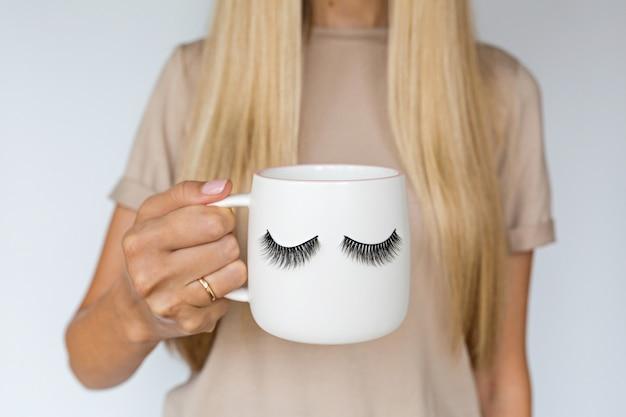 Mano femminile che tiene tazza con ciglia finte. Foto Premium