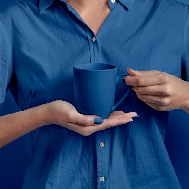 Mano femminile che tiene tazza Foto Gratuite