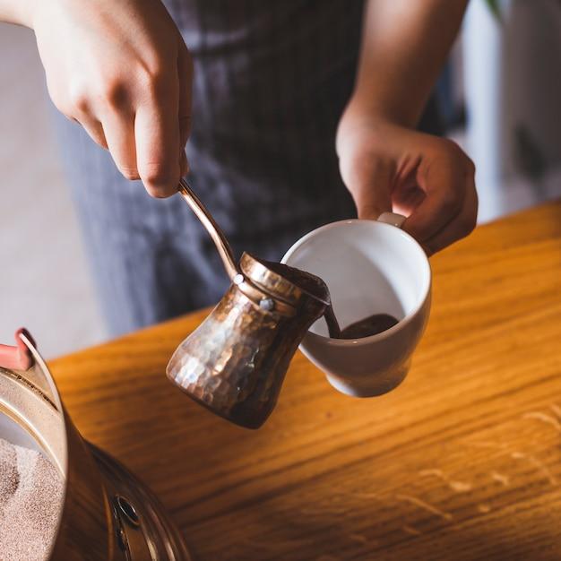 Mano femminile che versa caffè turco nella tazza ceramica bianca al ristorante Foto Gratuite