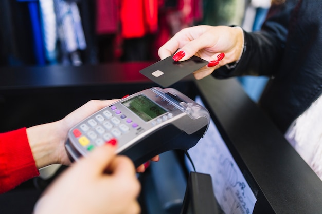 Mano femminile con la carta di credito che paga tramite il terminale per il pagamento nel negozio Foto Gratuite