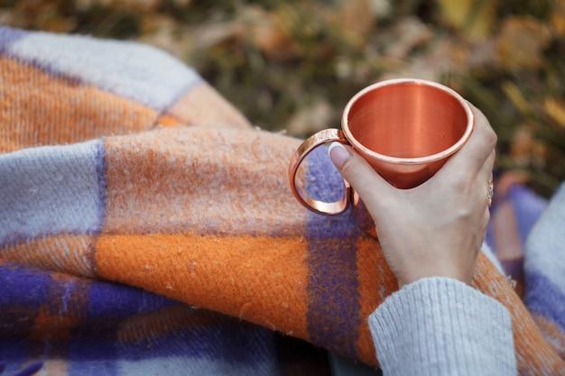Mano femminile del primo piano che tiene una tazza di rame brillante con tè Foto Premium
