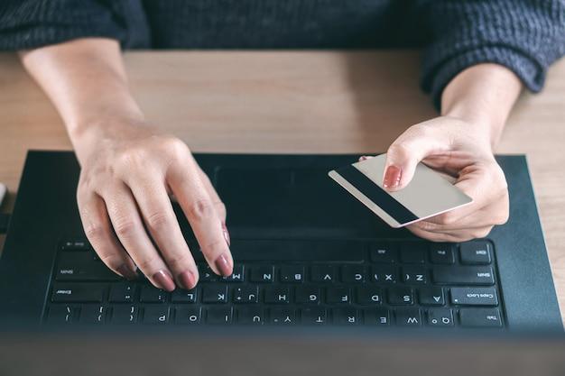 Mano femminile utilizzando la carta di credito acquisti online Foto Premium