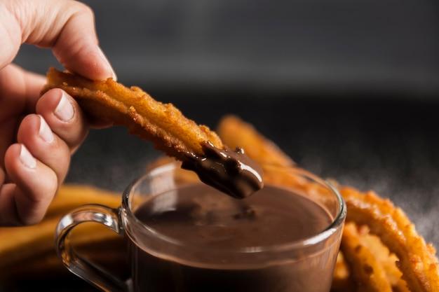 Mano immergendo un churros fritto nel cioccolato Foto Gratuite